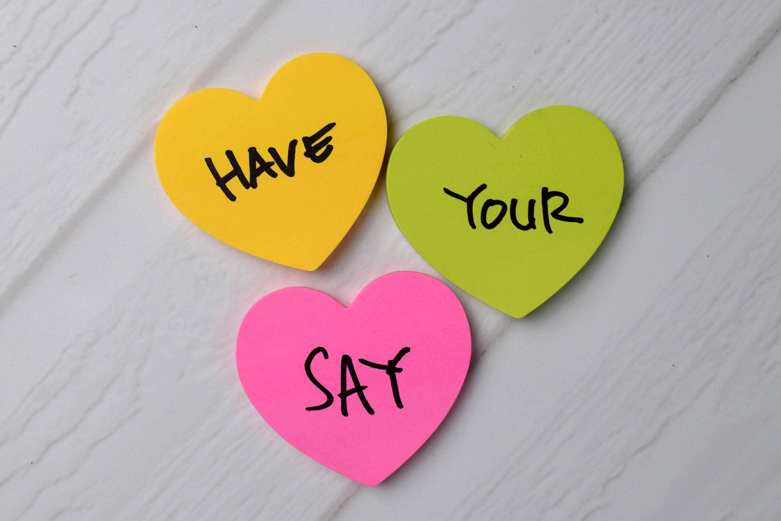 Have Your Say text on sticky notes with office desk.