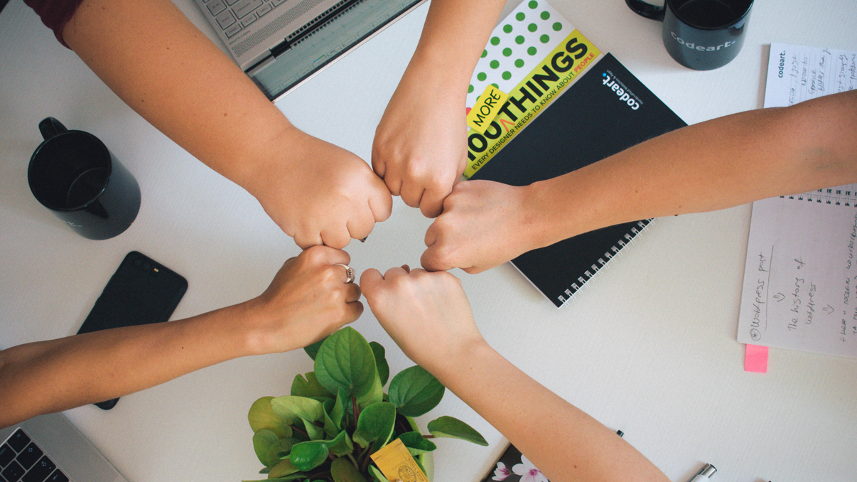 A team of five people fist bumping